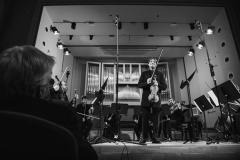 Czarno-białe zdjęcie. Na estradzie Piotr Pławner ze skrzypcami w dłoniach oraz Śląska Orkiestra Kameralna