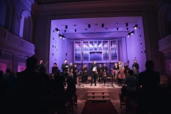 Na estradzie Piotr Pławner ze skrzypcami w dłoniach oraz Śląska Orkiestra Kameralna, publiczność podczas owacji na stojąco