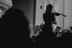 Czarno-białe zdjęcie. Koncertmistrzyni strojąca orkiestrę