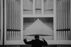 Czarno-białe zdjęcie dyrygenta tyłem na tle organów
