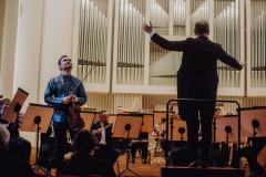 Na scenie Orkiestra Symfoniczna, Janusz Wawrowski oraz dyrygent Marcin Nałęcz-Niesiołowski