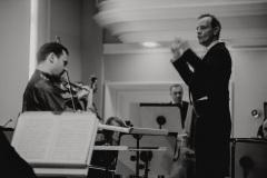 Czarno-białe zdjęcie. Dyrygent Marcin Nałęcz-Niesiołowski oraz solista skrzypek Janusz Wawrowski