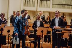 Dyrygent Marcin Nałęcz-Niesiołowski oraz solista skrzypek Janusz Wawrowski stojący podczas oklasków, w tle muzycy Orkiestry, również w pozycji stojącej