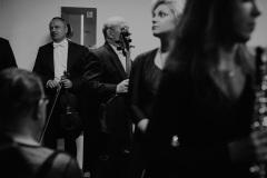 Czarno-białe zdjęcie muzyków przed koncertem za kulisami