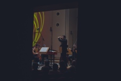 Czarno-białe zdjęcie. Maciej Tomasiewicz, Śląska Orkiestra Kameralna na scenie