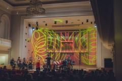 Widok na kolorowo oświetloną scenę, na której widoczni są Magdalena Maliszewska, Maciej Tomasiewicz i Śląska Orkiestra Kameralna