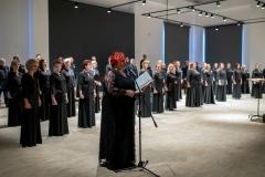 Chór Filharmonii Śląskiej na scenie Łaźni,  kobieta trzymająca teczkę (Regina Gowarzewska) zapowiadająca koncert przy mikrofonie