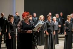 R2A6740Chór Filharmonii Śląskiej na scenie Łaźni,  kobieta trzymająca teczkę (Regina Gowarzewska) zapowiadająca koncert przy mikrofonie