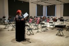 Zapowiadająca koncert kobieta (Regina Gowarzewska) przy mikrofonie, przed pustymi miejscami przygotowanymi dla orkiestry