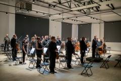Orkiestra Symfoniczna Filharmonii Śląskiej w pozycji stojącej, przed rozpoczęciem gry