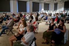 Publiczność zgromadzona w Łaźni, siedząca na krzesłach, w maseczkach zakrywających nos i usta