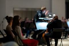 Orkiestra Symfoniczna Filharmonii Śląskiej pod batutą Szymona Bywalca rozmazana w tle, na pierwszym planie dwie dziewczynki siedzące w pierwszym rzędzie