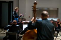 Szymon Bywalec - dyrygent - widoczny pośród muzyków sekcji wiolonczel i kontrabasów, siedzących tyłem