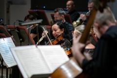 Zbliżenie na muzyków orkiestry - najwyraźniej widoczna altowiolistka
