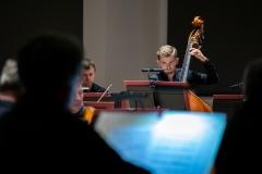 Kontrabasista orkiestry widoczny zza pleców siedzącego naprzeciw niego skrzypka