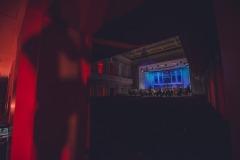 Kolorowo oświetlona scena widoczna  z tyłu sali