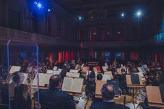 Orkiestra widoczna z perspektywy sceny, na drugim planie całość sali, pusta widownia.
