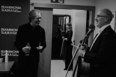 Czarno-białe zdjęcie. Muzycy orkiestry oraz dyrygent za kulisami