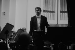 Czarno-białe zdjęcie. Pianista Zbigniew Raubo przy fortepianie