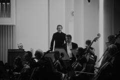 Czarno-białe zdjęcie. Dyrygent i solista wchodzący na scenę