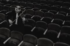 Czarno-białe zdjęcie. Skrzypek rozgrywający się na widowni.