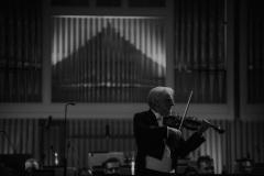 Czarno-białe zdjęcie.  Solista koncertu Rainer Honeck na scenie, za nim orkiestra i organy.