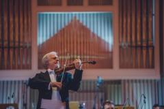 Solista koncertu Rainer Honeck na scenie, za nim orkiestra i organy.
