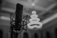 Czarno-białe zdjęcie. Mikrofon na sali koncertowej