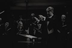 Czarno-białe zdjęcie. Jarosław Wolanin, Chór Filharmonii Śląskiej na scenie
