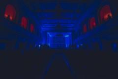 Sala koncertowa oświetlona ciemnogranatowymi światłami.