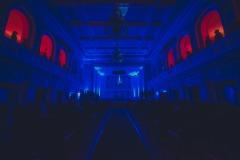 Sala koncertowa oświetlona ciemnogranatowymi światłami. Nad sceną hologram dyrygenta.