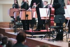 Widok na scenę z widowni, orkiestra stojąca przed rozpoczęciem koncertu, kłaniający się dyrygent