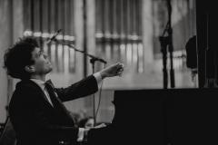 Czarno-białe zdjęcie. Solista koncertu Szymon Nehring przy fortepianie.