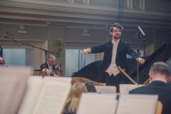 Dyrygent Yaroslav Shemet widoczny zza muzyków orkiestry.