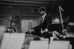 Czarno-białe zdjęcie. Dyrygent Yaroslav Shemet widoczny zza muzyków orkiestry.