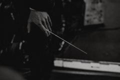 Czarno-białe zdjęcie. Batuta w dłoni dyrygenta.