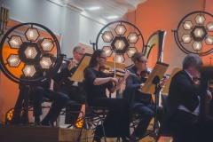 Sekcja skrzypiec Orkiestry Symfonicznej, lampy oświetlające scenę.