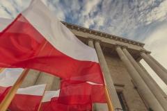 Biało-czerwone flagi, w tle niebo oraz gmach Archikatedry