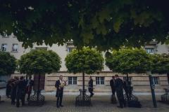 Muzycy przed budynkiem Archikatedry, pośród drzew