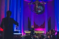 Solistka oraz widoczny z tyłu dyrygent, w tle kolorowo oświetlony ołtarz oraz krzyż