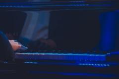 Zbliżenie na dłonie pianisty oraz klawiaturę fortepianu
