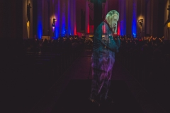 Hologram Henryka Mikołaja Góreckiego widoczny na tle kolorowo oświetlonego ołtarza