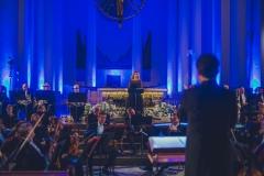 Dyrygent (widoczny od tyłu) oklaskujący solistkę
