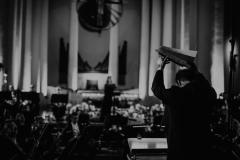Czarno-białe zdjęcie dyrygenta z uniesioną wysoko partyturą