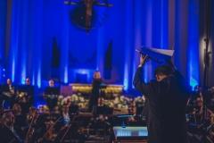 Kolorowe zdjęcie dyrygenta z uniesioną wysoko partyturą