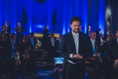 Dyrygent, w tle stojąca orkiestra