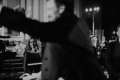Solistka widoczna zza ramienia dyrygenta
