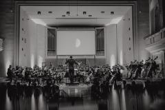 Czarno-białe zdjęcie.  Widok na scenę, wyświetlona grafika przedstawiająca planety.