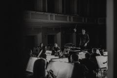 Czarno-białe zdjęcie. Orkiestra i dyrygent widoczni zza kulis