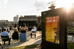 Plac Fajrant na terenie Muzeum Śląskiego, na pierwszym planie afisz informujący o datach koncertów w ramach Sezonu Letniego